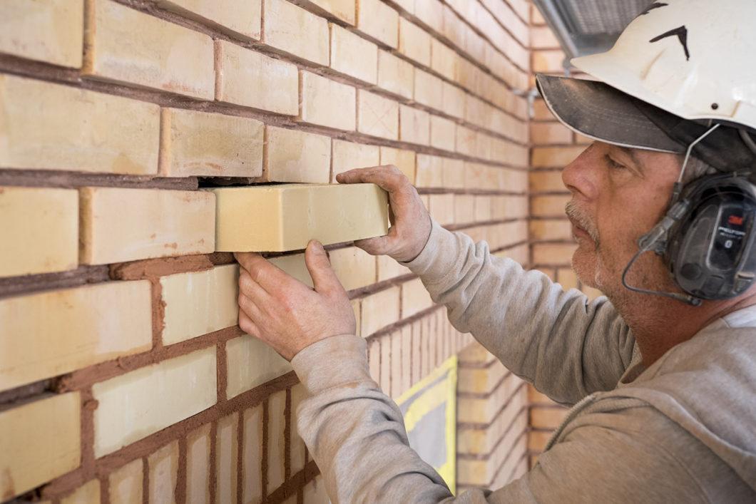 Man med skyddshjälm byter tegelstenar i en fasad