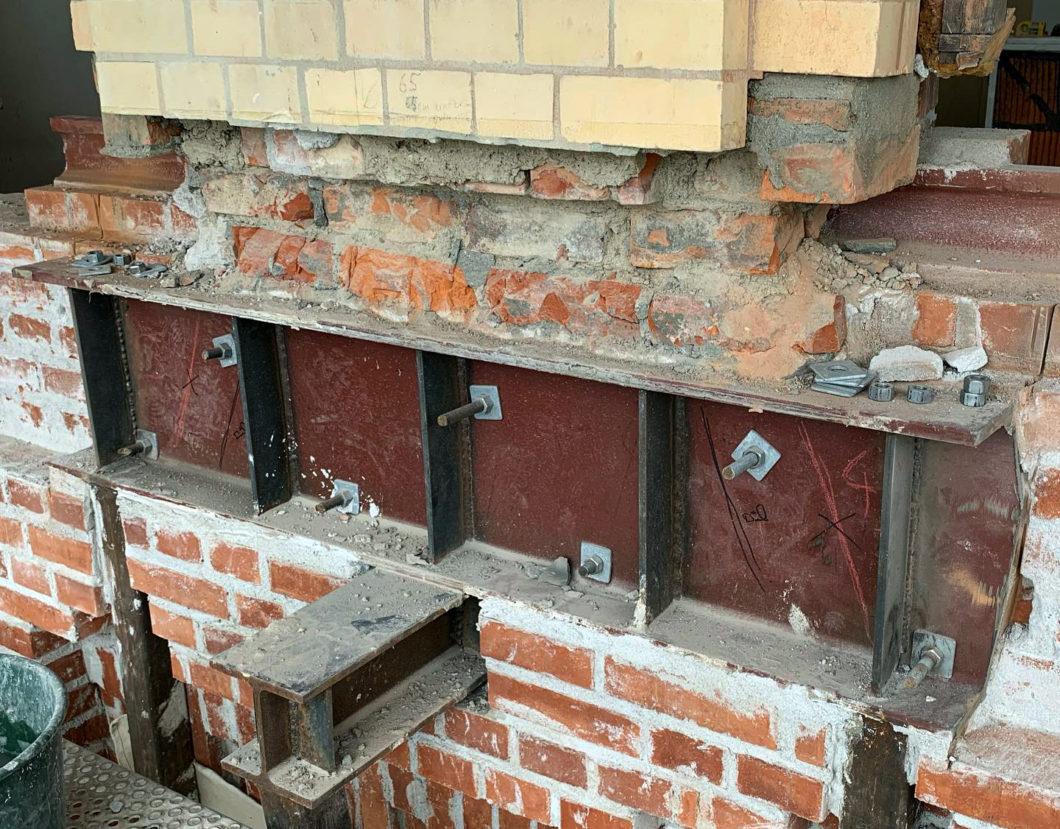 Tillfällig stålkonstruktion under sektion av tegelfasad